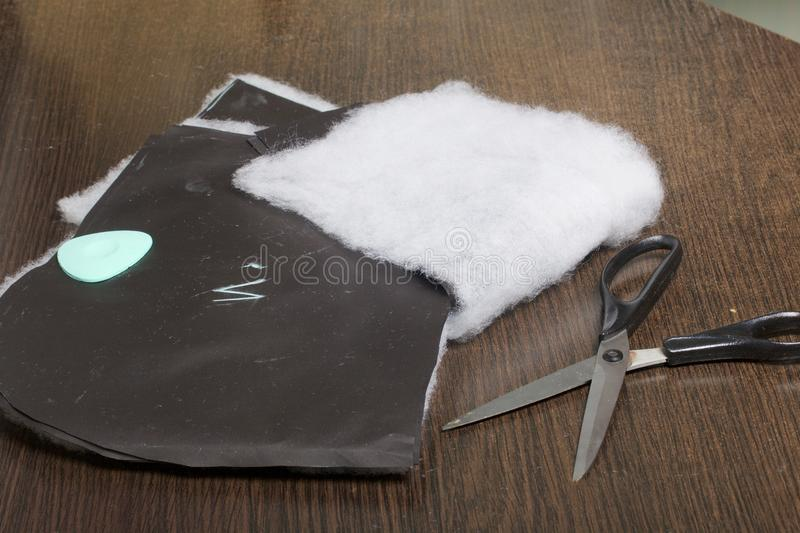 Cutting of the product for sewing. On the table is a cloth with chalk-marked garments. Just lie scissors and chalk. Cutting of the product for sewing. On the stock photos