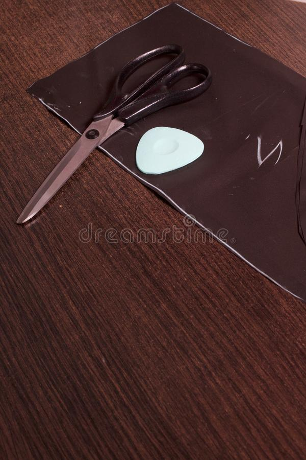Cutting of the product for sewing. On the table is a cloth with chalk-marked garments. Just lie scissors and chalk. Cutting of the product for sewing. On the royalty free stock images