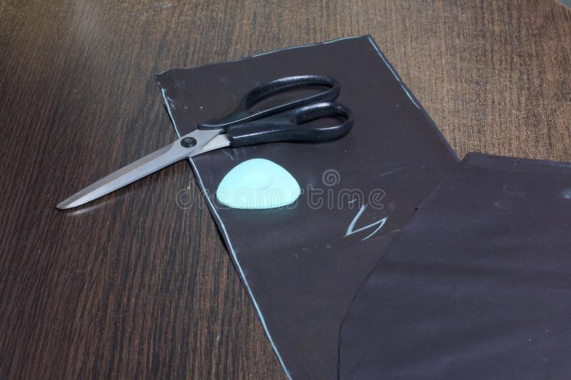Cutting of the product for sewing. On the table is a cloth with chalk-marked garments. Just lie scissors and chalk. Cutting of the product for sewing. On the royalty free stock image