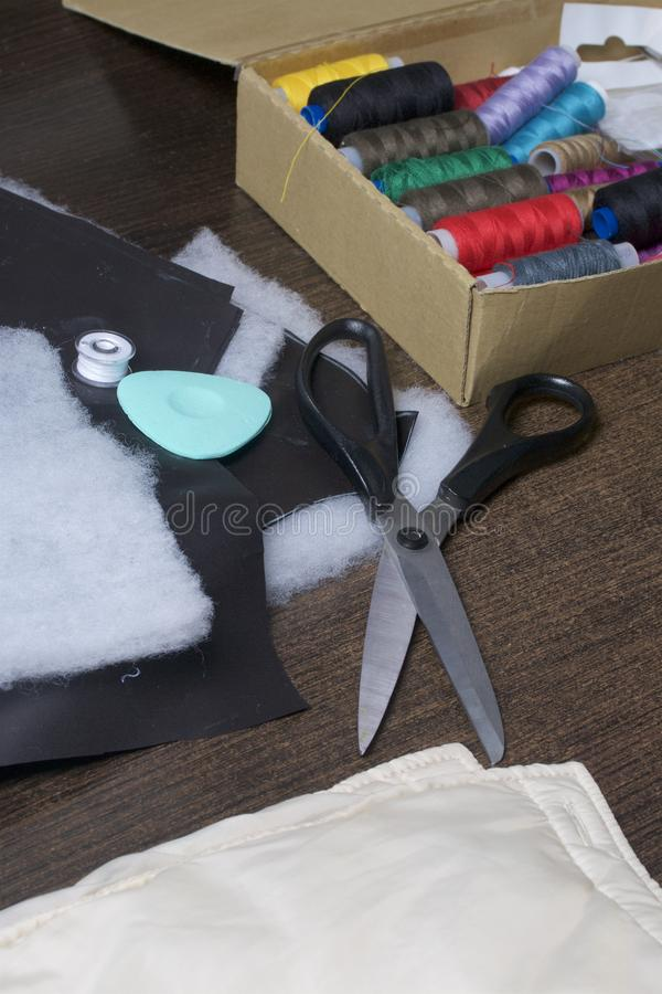 Cutting of the product for sewing. On the table is a cloth with chalk-marked garments. Nearby lie scissors, chalk and a box with c. Olorful threads royalty free stock photography