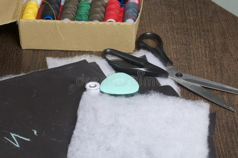 Cutting of the product for sewing. On the table is a cloth with chalk-marked garments. Nearby lie scissors, chalk and a box with c. Olorful threads stock photos