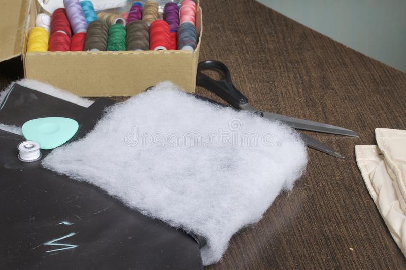 Cutting of the product for sewing. On the table is a cloth with chalk-marked garments. Nearby lie scissors, chalk and a box with c. Olorful threads stock image