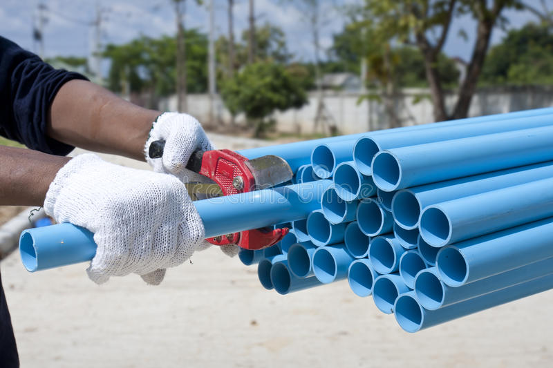 Cutting PVC pipe. In construction site royalty free stock image