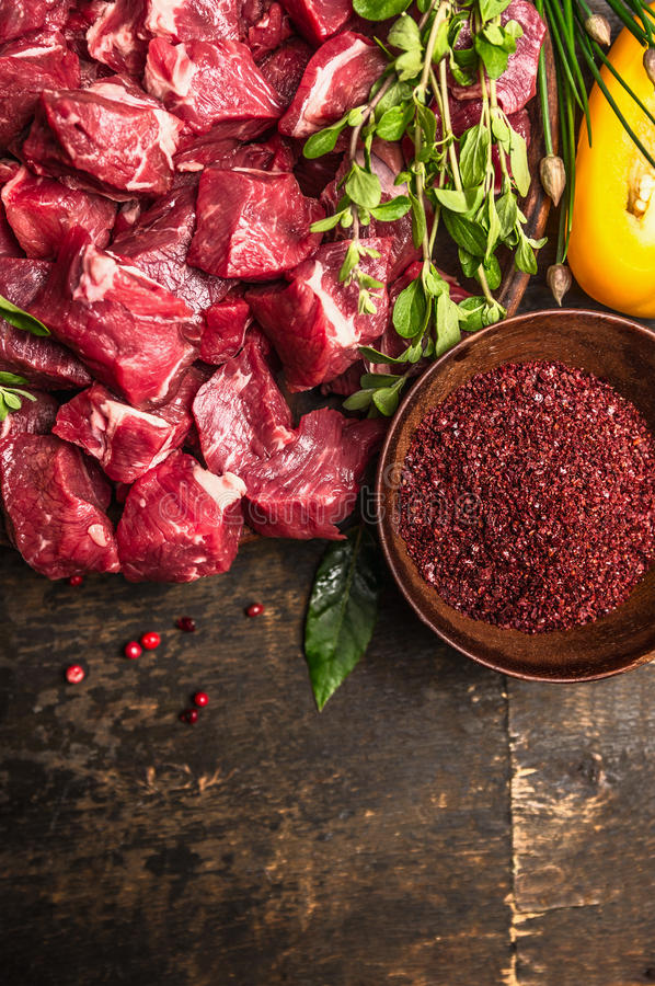 Cutting raw meat with spices and fresh herbs , ingredients for goulash cooking on rustic wooden background, top view stock image