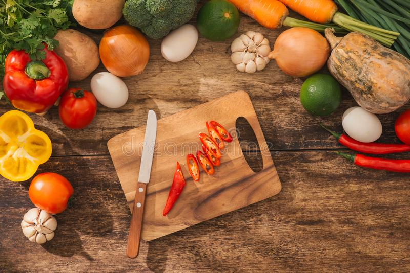 Cutting red chili. Male hands cooking vegetables salad in kitchen. Top view. royalty free stock images