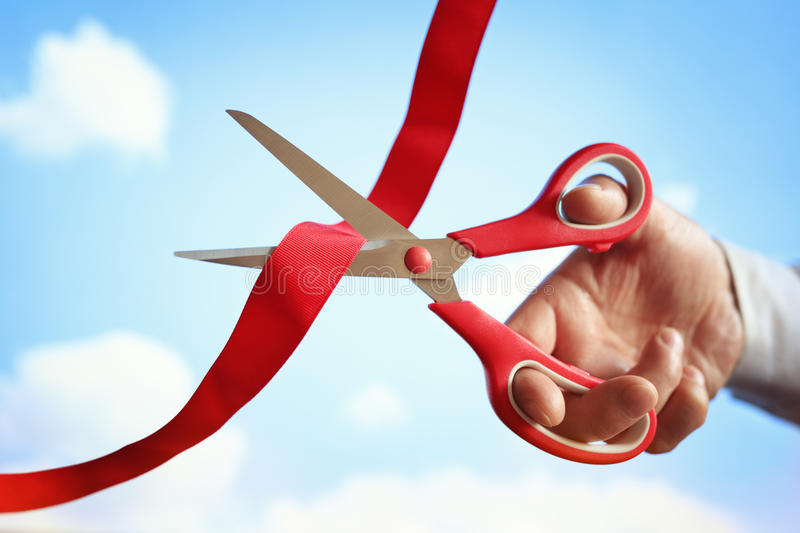 Cutting red ribbon with scissors. Businessman cutting a red ribbon with a pair of scissors at opening ceremony stock photography