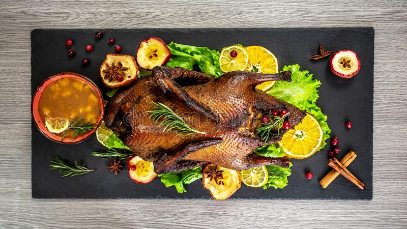 Cutting the roast duck and oranges on a black slate board. horizontal view from above. Food concept stock photos