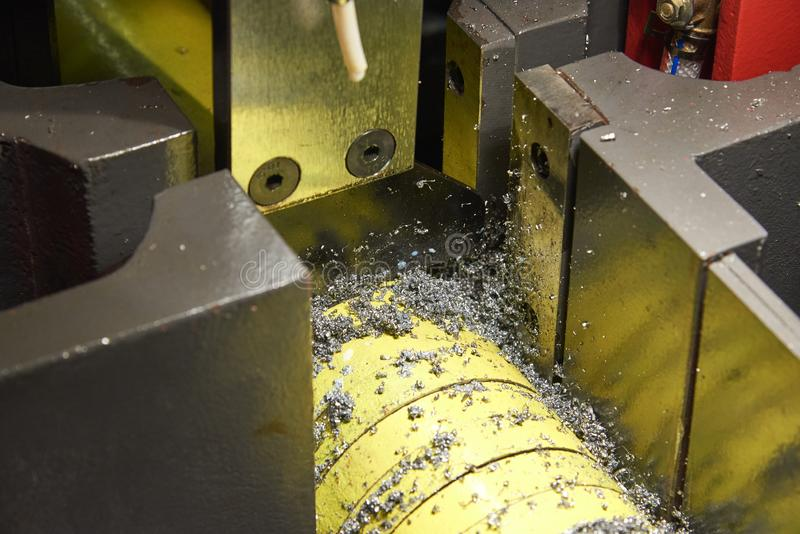 Cutting a round metal bar with a band saw. Chips and drops of oil fly out of the cutting area. Cutting a round metal bar with a band saw.  Chips and drops of oil royalty free stock photography