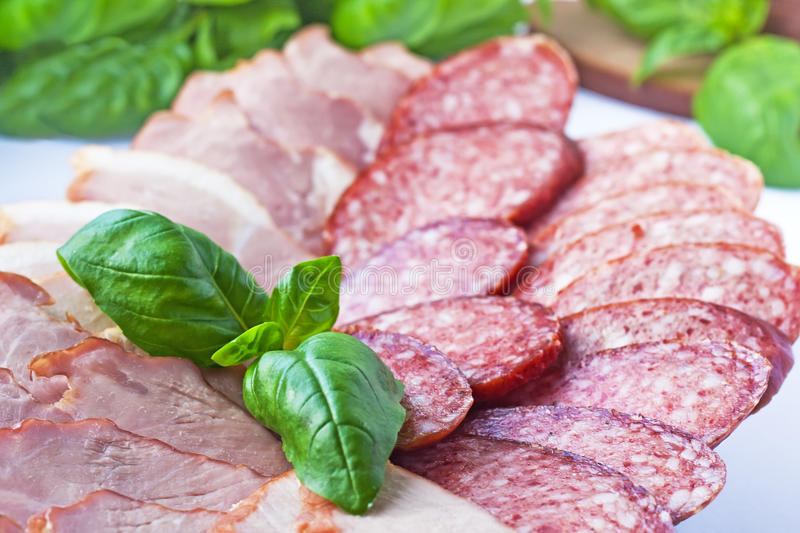 Cutting sausage and cured meat royalty free stock photos
