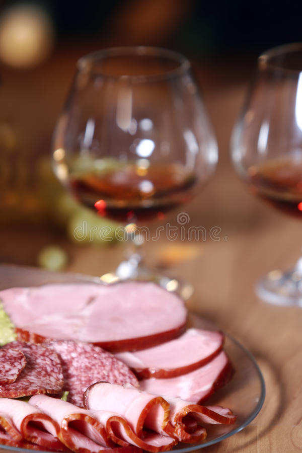 Cutting sausage, cured meat and glass of cognac stock photo