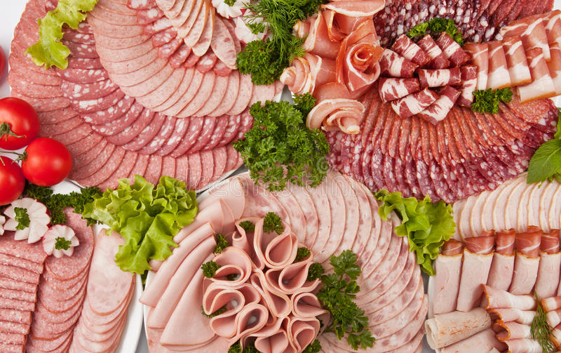 Cutting sausage and cured meat with a parsley on the white plate stock image