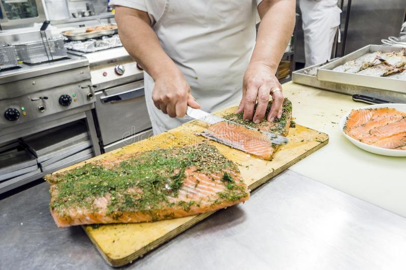 Cutting into slices a big fillet of delicious salmon royalty free stock photos