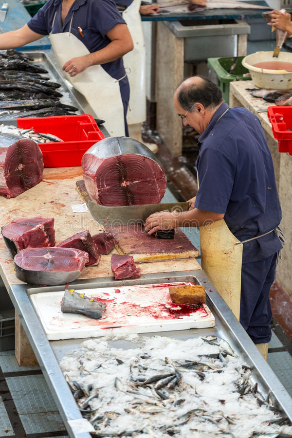 Cutting tuna steaks at fish market Mercado dos Lavradores. Funchal, royalty free stock photography