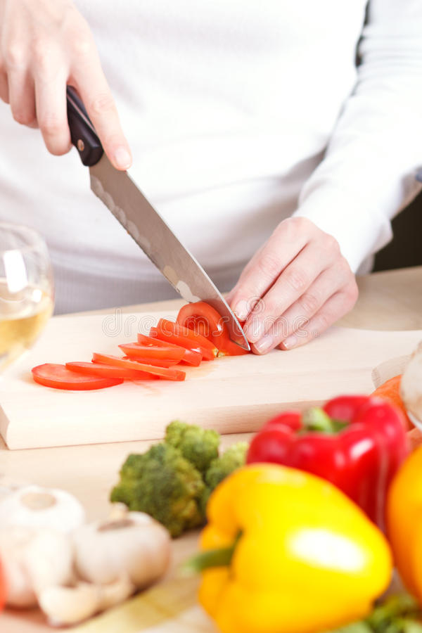 Cutting vegetables. In the kitchen stock images