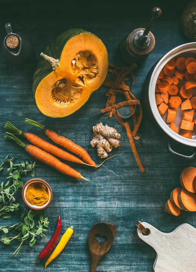 Cutting vegetables for pumpkin soup or vegetarian stew on kitchen table with pot, cutting board and orange ingredients. Carrots, sweet potatoes, turmeric and stock photo