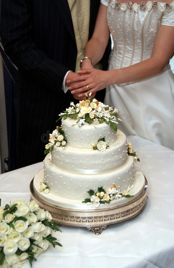 Cutting The Wedding Cake. Hands of a bride and groom holding a knife together and cutting into their wedding cake. Bride and groom shown from the neck down royalty free stock image