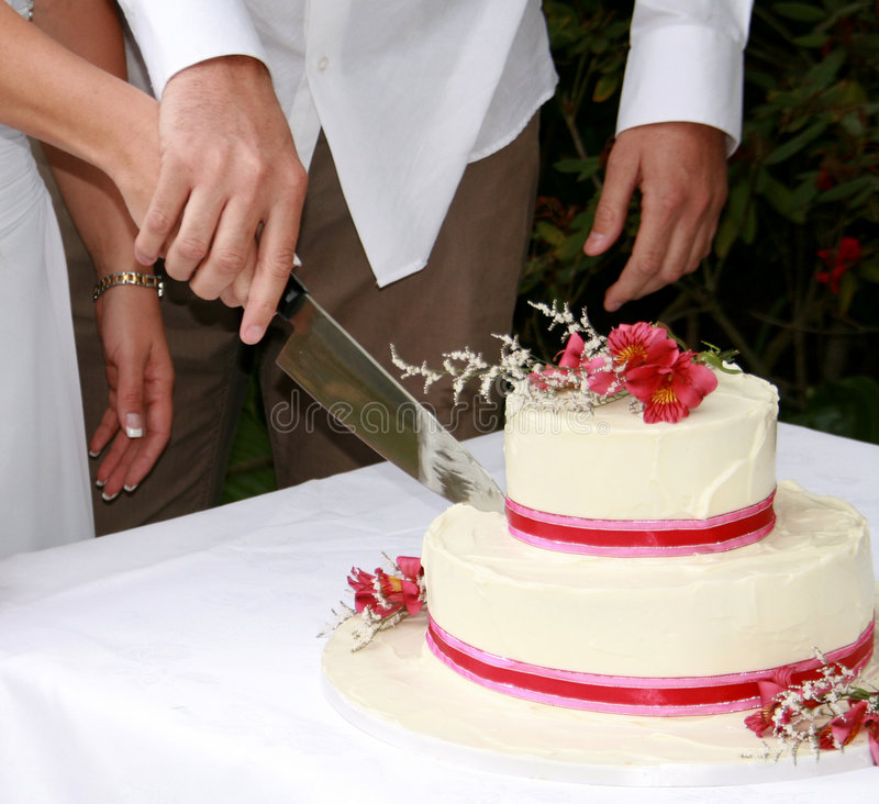 Cutting the Wedding Cake. A Bride and Groom cutting their wedding cake together stock photography