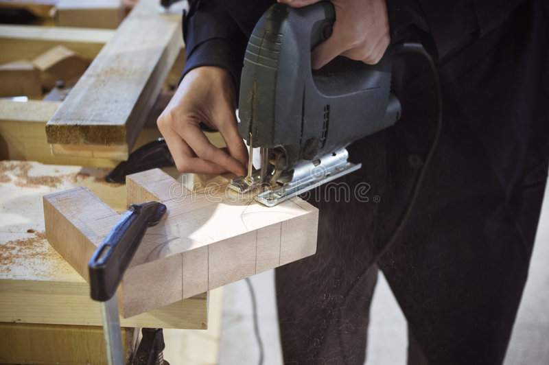 Cutting wood with jigsaw stock images