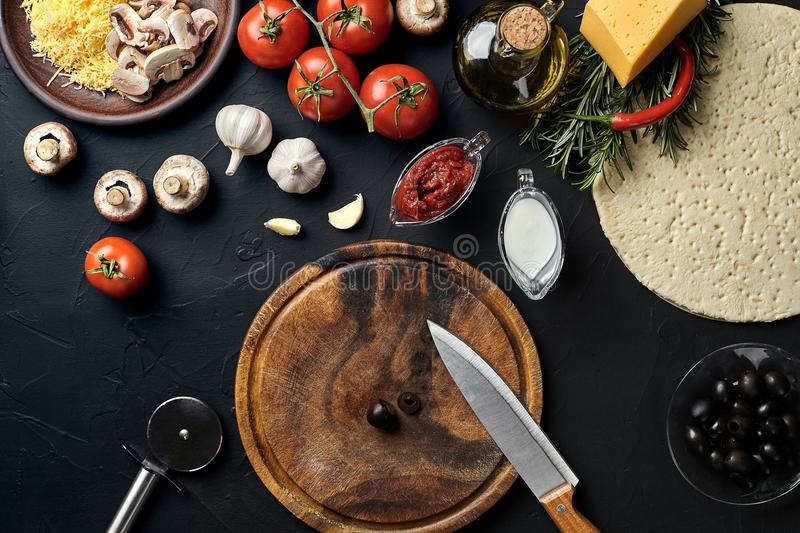 Cutting wooden board with traditional pizza preparation ingredients: cheese, tomatoes sauce, olives, olive oil, pepper royalty free stock images
