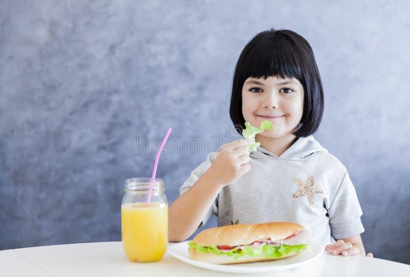 Cuttle το μαύρο μικρό κορίτσι τρίχας που έχει το πρόγευμα και τρώει το μαρούλι στοκ φωτογραφίες