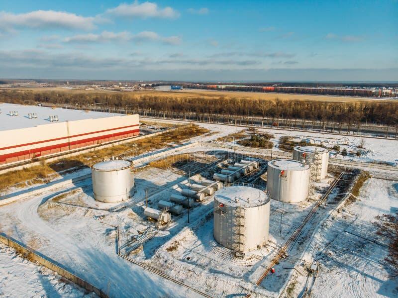 Cuves de stockage d'acier ou en métal pour le pétrole ou le carburant près du bâtiment industriel d'entrepôt ou d'usine en hiver, image stock