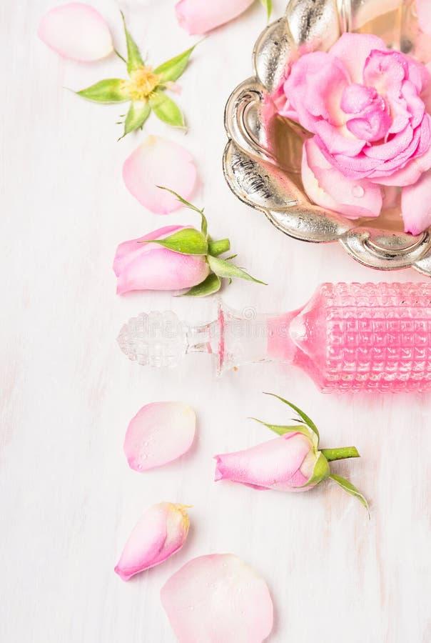 Cuvette argentée avec des roses dans l'eau, la bouteille en cristal et des bourgeons roses sur en bois blanc photo stock