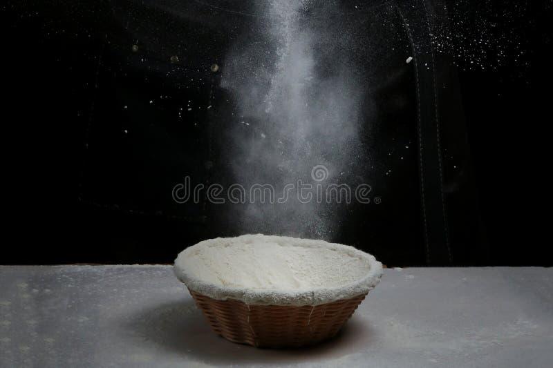 Cuvette avec de la farine sur l'éclaboussure noire sur le fond noir photos stock
