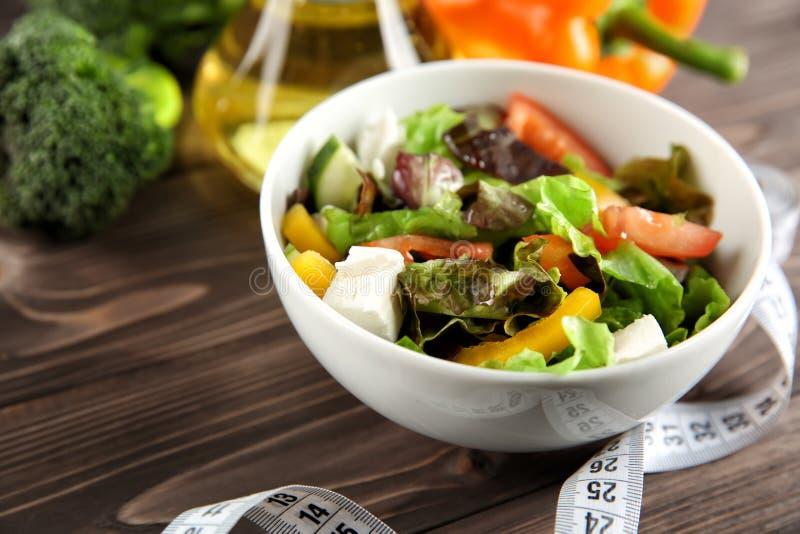 Cuvette avec de la salade de légume frais et la bande de mesure sur la table Suivez un r?gime la nourriture photos libres de droits