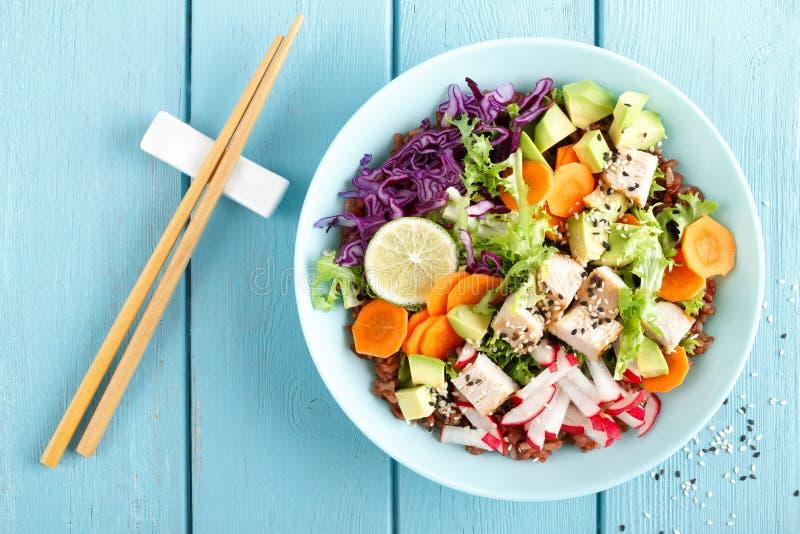 Cuvette avec de la salade de viande grillée de poulet, de riz brun et de légume frais de l'avocat, du radis, du chou frisé de cho photo stock