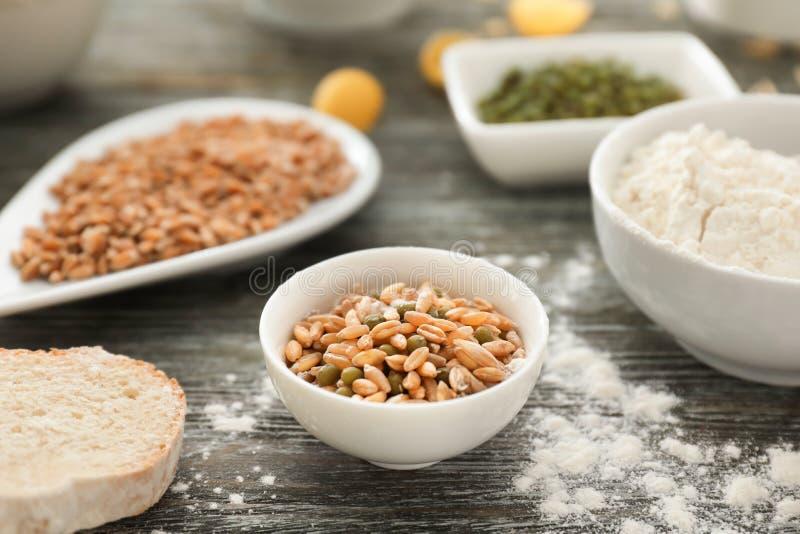 Cuvette avec des grains et des haricots de blé sur la table en bois images libres de droits