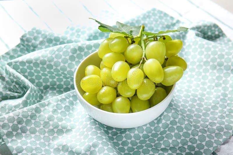 Cuvette avec des raisins mûrs frais sur la serviette image stock