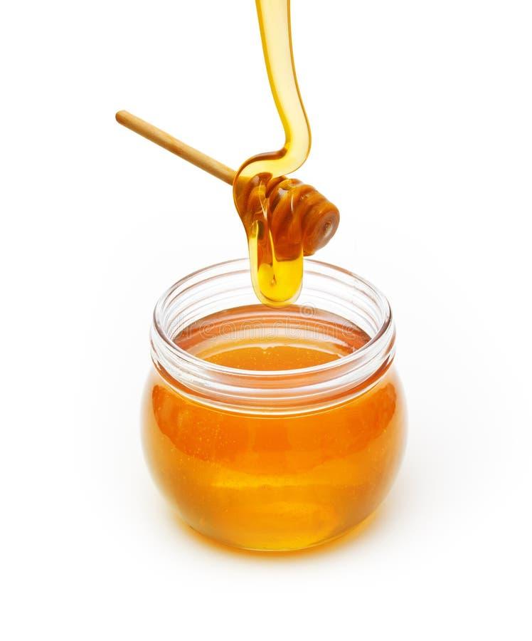 Cuvette avec du miel et le plongeur en bois photos stock