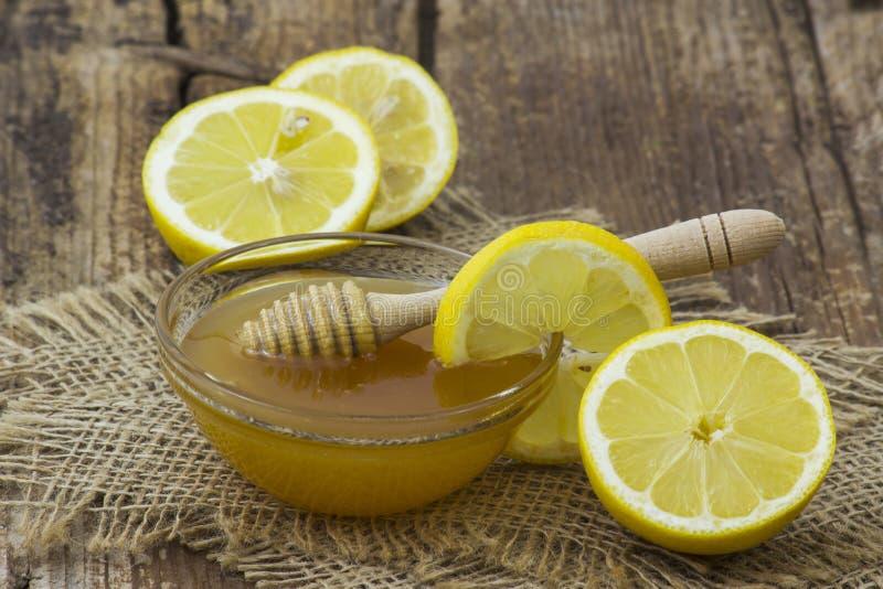 Cuvette avec du miel et les citrons frais images stock