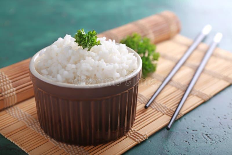 Cuvette avec du riz blanc et les baguettes bouillis sur le tapis en bambou photographie stock libre de droits