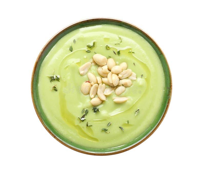 Cuvette avec la soupe et les arachides savoureuses à courgette sur le fond blanc images stock