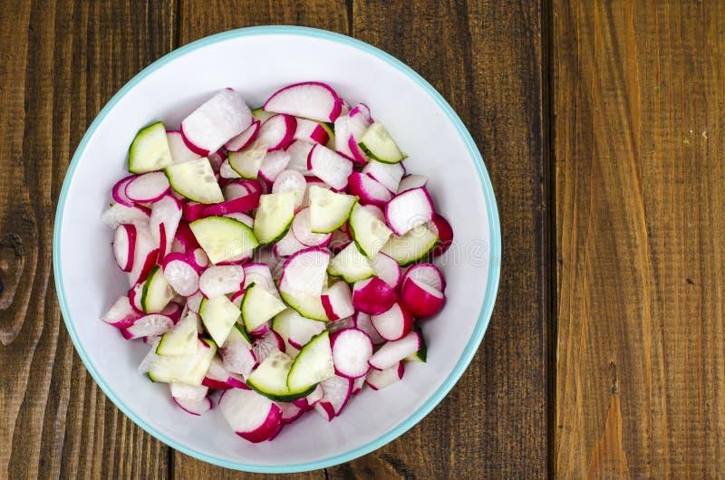 Cuvette avec le radis et le concombre frais coupés en tranches, nourriture végétarienne photos stock