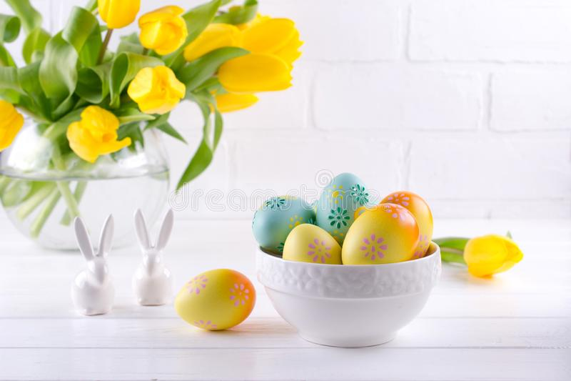 Cuvette avec les oeufs de pâques colorés, décoration de Pâques de ressort sur la table en bois blanche avec le bouquet des fleurs image libre de droits