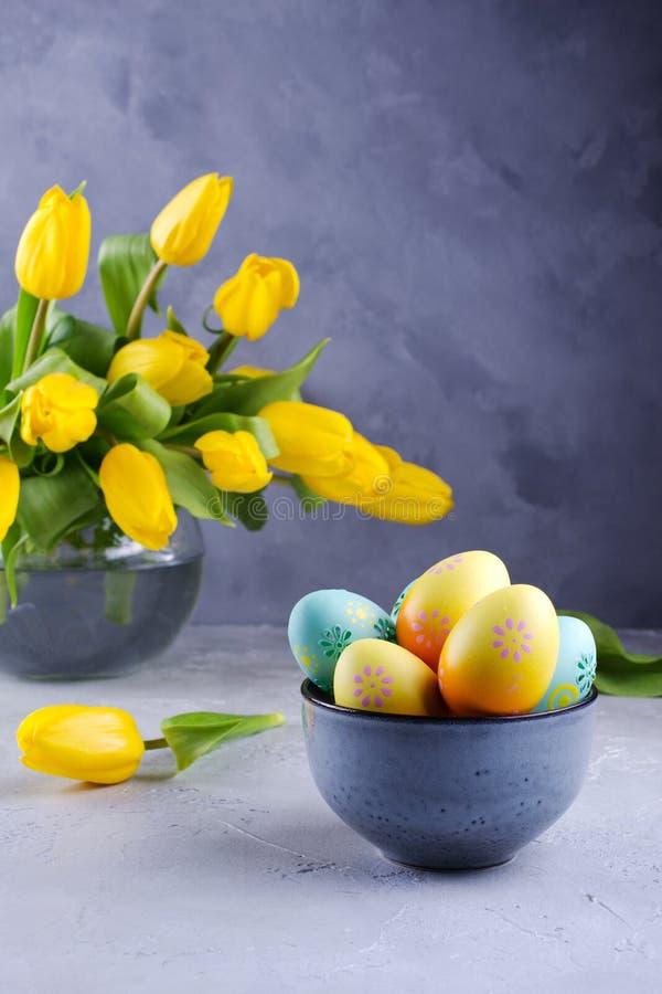 Cuvette avec les oeufs de pâques colorés ; décoration de Pâques de ressort sur la table grise avec le bouquet des fleurs jaunes d image stock