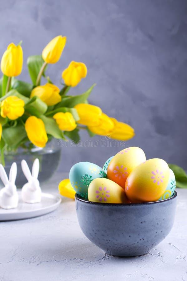 Cuvette avec les oeufs de pâques colorés ; décoration de Pâques de ressort sur la table grise avec le bouquet des fleurs jaunes d images libres de droits