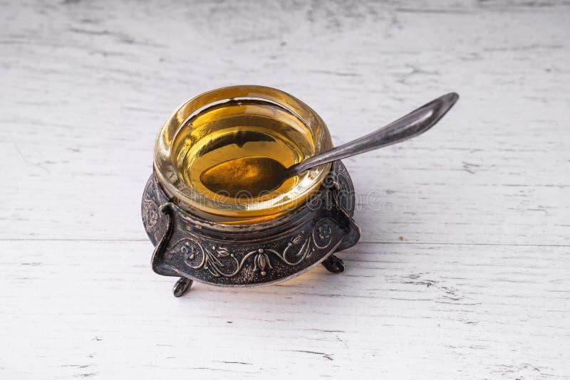 Cuvette avec une cuillère avec de l'argent antique de miel image libre de droits