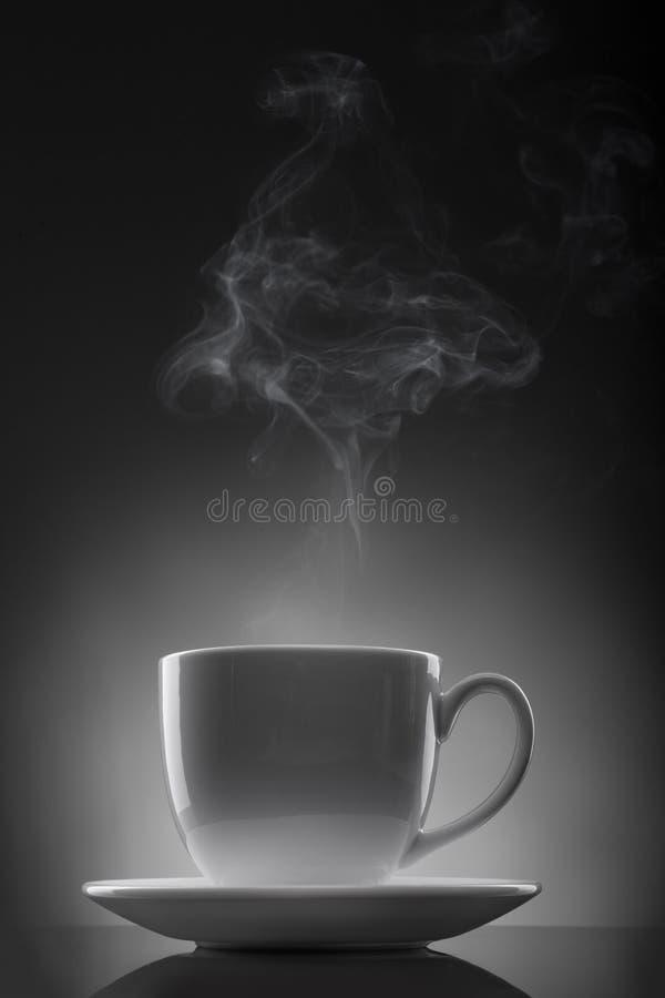 Cuvette blanche avec le liquide chaud et vapeur sur le noir photographie stock