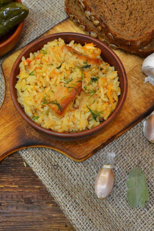 Cuvette d'argile de vintage avec le pilaf épicé traditionnel de nourriture, cuvette avec les concombres marinés, tranches de pain images libres de droits