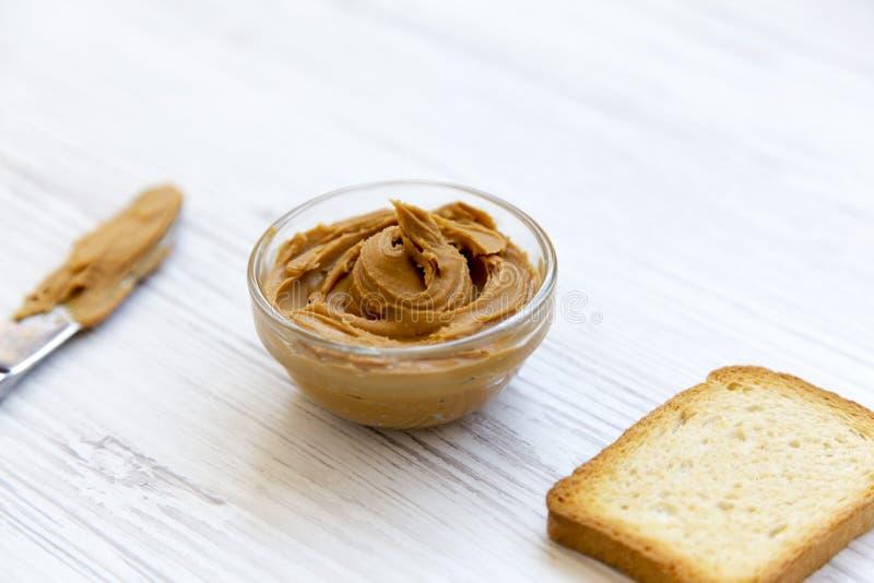 Cuvette de beurre, de pain grillé et de couteau d'arachide au-dessus du fond en bois blanc, photo stock