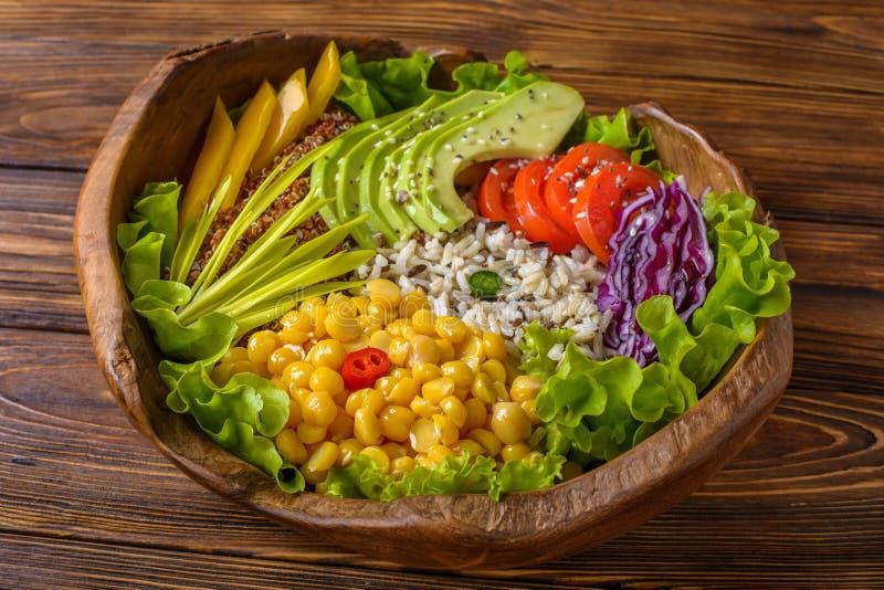 Cuvette de Bouddha avec le pois chiche, avocat, zizanie, graines de quinoa, paprika, tomates, verts, chou, laitue sur brun br?l?  photo stock
