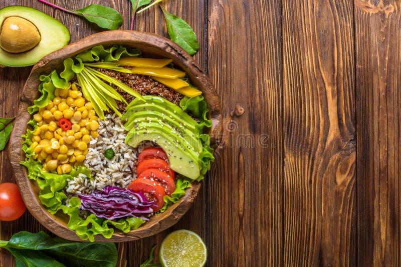 Cuvette de Bouddha avec le pois chiche, avocat, zizanie, graines de quinoa, paprika, tomates, verts, chou, laitue sur brun br?l?  photos stock