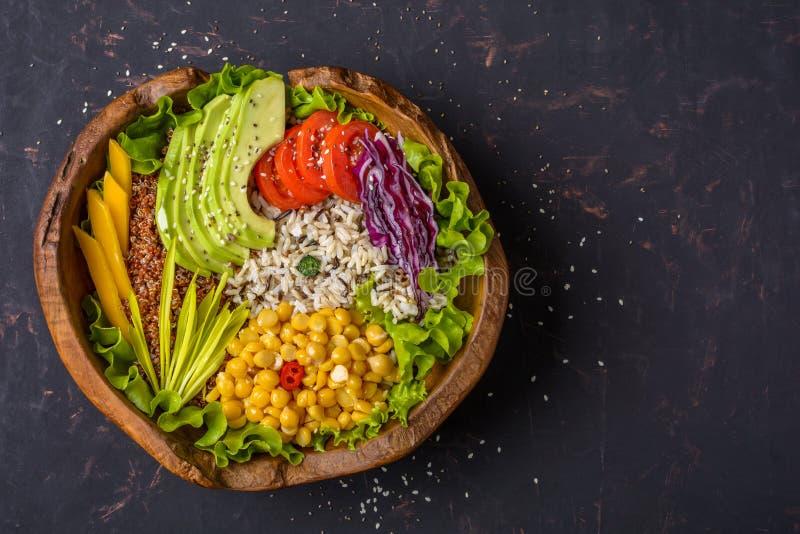 Cuvette de Bouddha avec le pois chiche, avocat, zizanie, graines de quinoa, paprika, tomates, verts, chou, laitue sur la pierre f photographie stock libre de droits