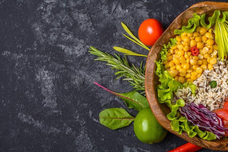 Cuvette de Bouddha avec le pois chiche, avocat, zizanie, graines de quinoa, paprika, tomates, verts, chou, laitue sur la table en photo stock