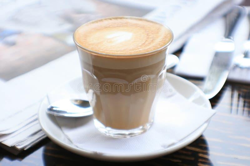 Cuvette de café avec le papier de nouvelles sur la table photo stock