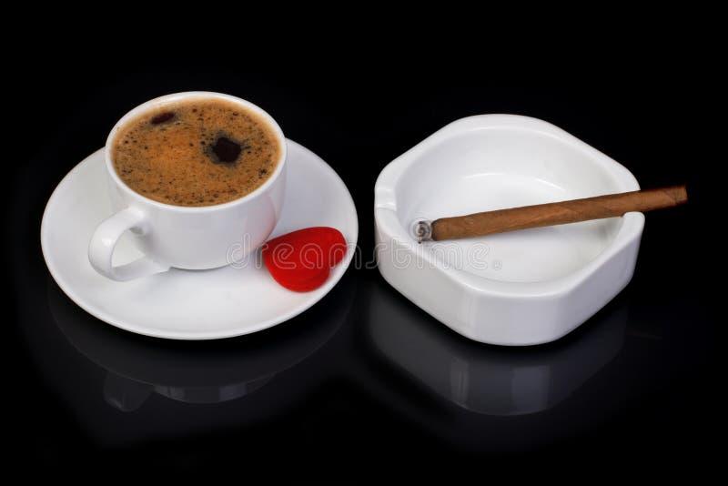 Cuvette de café décorée d'une proue et d'un coeur. Cigare et cendrier photographie stock