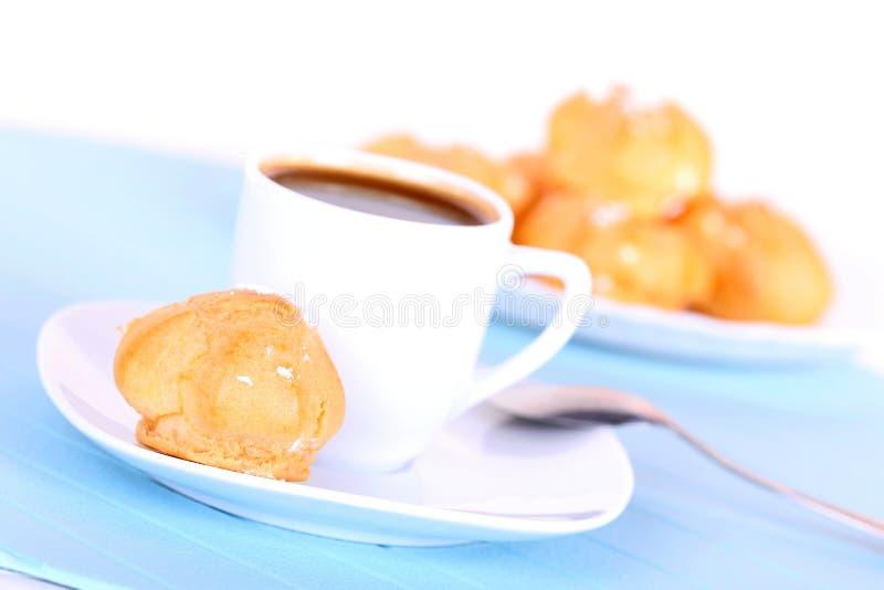 Cuvette de café et de gâteaux savoureux sur le couvre-tapis bleu image libre de droits